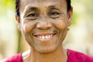 Das Portrait einer Chin Frau mit der traditionellen Gesichtstätowierung in Mrauk U, Myanmar