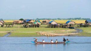 Ein Traditionelles Boot auf dem Kaladan Fluss vor einem Dorf in dem Rakhine State in Myanmar vorbei .