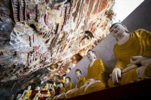 Viele Buddha Statuen und religiöse Schnitzereien auf den Kalkfelsen in der heiligen Kaw Goon Höhle in Hpa An, Myanmar (Burma) ein toller Stop bei jeder Rundreise durch Myanmar